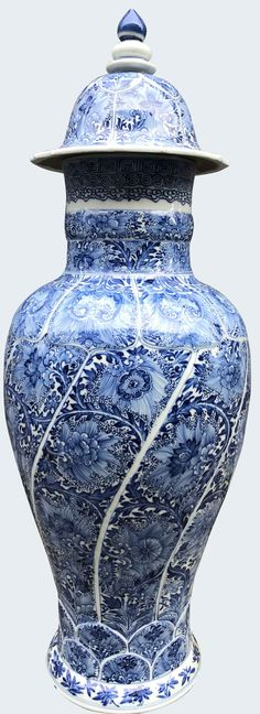 A very tall Chinese blue and white baluster vase and cover. Kangxi period Of slender baluster form, moulded and decorated with swirling panels enclosing flowers, between lappet-shaped floral panels and shoulder, the domed cover similarly decorated with stepped finials. China. Qing. Porcelain.