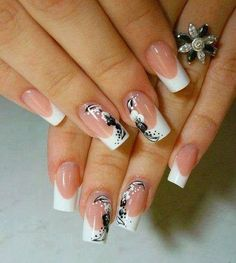White French tips with floral details painted in black polish. Make your nails truly stand out with these elegant looking flower designs painted on top of them.