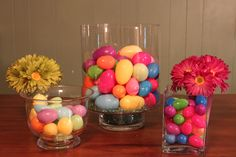 Table decoration for Easter...colorful eggs in glass containers with bright colored flowers