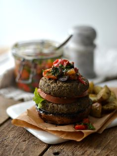 Lentil burgers on Portobello mushrooms topped with roasted bell pepper tomato mediterranean salad