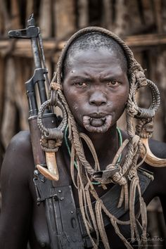 Mursi Tribe Woman holding a Kalashnikov and wearing Pig Fangs, Omo Valley, Ethiopia - JOEL SANTOS - Photography Tribes Of The World, People Around The World, Fille Gangsta, Africa People, Mursi Tribe, Tribal Warrior, Indigenous Tribes, Photo Portrait, Tribal People