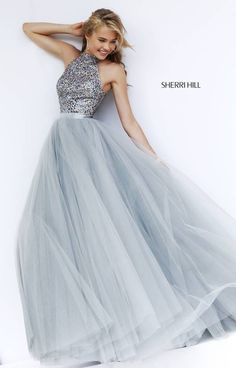 Lose yourself in the impossibly romantic Sherri Hill 11316 full-length dress. This gorgeous gown showcases a shimmering beaded bodice with halter neckline. The ball gown skirt is a glorious froth of layered airy tulle that is fabulously feminine, and features a sleek satin waistband.