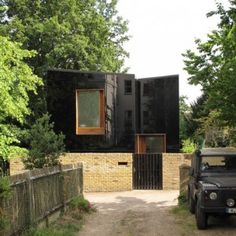 Black glass facade mirrors scenery at  south London home by Ian McChesneyThe two timber-framed volumes are clad in sections of black polished glass, favoured by the planning committee for its perceived ability to blend into the surroundings. A layer of insulation between the prefabricated wooden frame and glass facing gives the house warmth.
