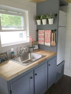 In the galley kitchen are blue-grey cabinets, butcher block counters, a four-burner gas stove, and an apartment size refrigerator. kleine wohnung küche Wanigan by Burrow Tiny Homes - Tiny Living Apartment Size Refrigerator, Small Apartment Kitchen, Small Apartment Decorating, Apartment Ideas, Small Kitchen Decorating Ideas, Basement Apartment Decor, Small Apartment Furniture, Apartment Interior, Condo Kitchen