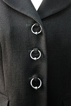Винтажный жакет Moschino Cheap nand Chic выполнен из черной шерстяной ткани. Слегка приталенный силуэт, отложной воротник, фронтальная застежка на на пуговицы в виде колец.  Идеальное винтажное состояние.