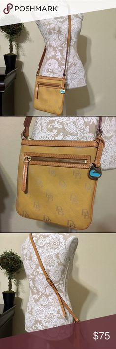 """Vintage Dooney & Bourke Crossbody Purse 👛 Dooney & Bourke Crossbody Purse 👛Vintage Dooney & Bourke Crossbody Purse is a muted gold color with the letters DB stitched in gray. Measures 8""""x8"""" with a 5"""" deep zipper pocket in front. Has a small zipper pocket inside along with a 2"""" wide open pocket. 19"""" drop from shoulder with a 6"""" extension. Pictured with the extension NOT in use. Has some minor flaws as pictured. Have cleaned to the best of my ability. Is in great pre-loved condition! Dooney…"""