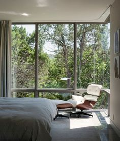 Bedroom with reading corner and floor-to-ceiling windows.