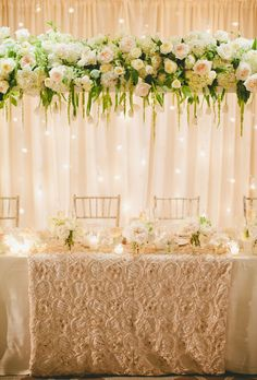 Brides.com: . A stunning overhead centerpiece of muted roses and draping tulips suspends above the bridal party table in ethereal beauty, complemented by a backlit wall of twinkling lights. Coupled with a minimal tabletop set with candles, the look creates a soft glow and magical ambiance.