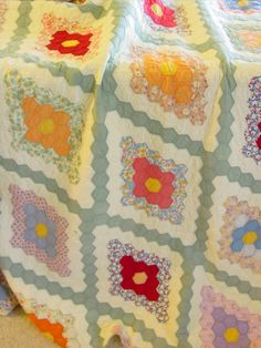 Field of Diamonds vintage quilt. This pattern is really a variation of the traditional flower garden quilt. The pattern is made in a diamond shape that gives if the field of hexagonal diamonds. All hand quilted around each piece at 7 spi. The separate green binding is also hand bound. Lots of colorful prints were used in making the quilt. Southwest Missouri area