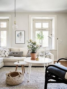 Bright living space with a large cream sectional sofa, layered coffee tables, and a industrial floor lamp