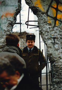 Berlin Wall, across the divide    An East German soldier looks through an open section of the Berlin Wall into the brave new world of West Berlin, 1989