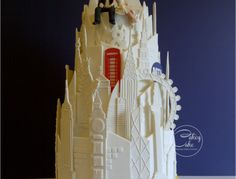 """This 4 tier wedding cake was designed and made for a jet-setting couple who wanted it to reflect the cities they have lived in (London, Hong Kong & New York) and include their love of skiing/boarding. The wedding celebration was also held at the very top of London's iconinc Gherkin building, so the cake needed to reflect the splendour of its surroundings! The cakes were 12"""" chocolate, 10"""" red velvet, 8"""" vanilla and 6"""" battenberg (a first for me, and the groom's favourite!). The iconic…"""