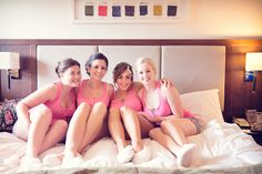 Bride and bridesmaids on bed in matching pink pajamas by one thousand words wedding photographers www.onethousandwords.co.uk