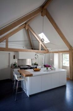 Kitchen in curved oak framed house in Hampshire, UK. By Roderick James Architects.
