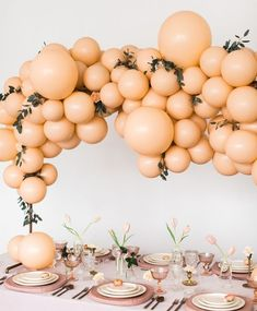 giant balloon arch in peach and pink pastel hues // modern bridal shower or easter tablescape