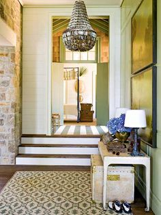 Love everything about this entry way -- the wall color, the rug, the pendant light, the old chest, the lamps, the hydrangeas, the stone wall, the wood paneling, the landscape paintings + beautiful photography | Bill Ingram's Lake Martin House from Southern Accents