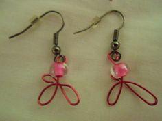 Des boucles d'oreilles fait de perles de verres et d'un motif en fils de fer rose métallique!