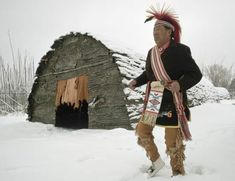 Photograph:A traditionally dressed Iroquois man chants and dances outside a reconstructed traditional longhouse.