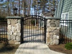 Wrought iron fence with stone columns... We could do this with brick instead of stone so it goes with our house
