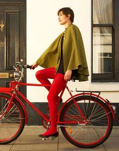 マントの色とタイツの赤と自転車の赤のコーデが素敵