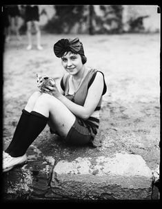 Mildred Katleck and opossum at bathing beach, 1922 Why is she holding a possum??