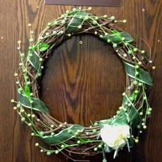 Easy spring door wreath. Twig wreath, greenery sprigs, ribbon, and a hair rosette. Cheap and simple.