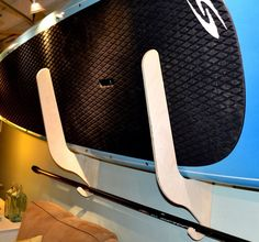 A wooden SUP rack that stores paddleboards horizontally against the wall.
