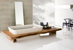 Platform bathtub on a wooden rectangular foundation. A mirror is attached to the tub and leans against the wall. Modern in design and very efficient in use.
