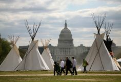 """People walk past teepees that are on the National Mall in Washington as part of a protest against the keystone pipeline. As part of its """"Reject and Protect"""" protest, the Cowboy and Indian Alliance is organizing a week-long series of actions by farmers, ranchers and tribes to show their opposition to the pipeline. 04/2014"""