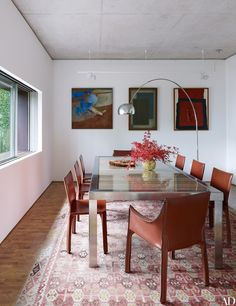 Artworks by, from left, Y. Mahalyi, Arcangelo Ianelli, and Tomie Ohtake survey the dining room's Estudio Campana table.