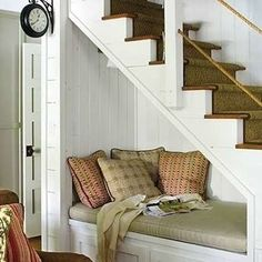 Bench Under Stairs: Cozy Reading Nook A simple banquette piled with pillows and lit from above with a wall sconce is a tempting spot to curl up with a favorite book. Drawers or cabinets below provide additional storage for the room.