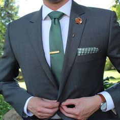 Hunter green skinny pin dot tie paired with a gray suit.