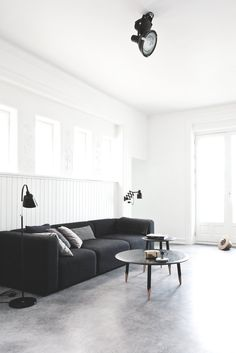 Scandinavian living room with concrete floor. Vedbaek House IV by Norm.Architects. Features with black sofa, &Tradition Hoof Table SW1, Hoof Table SW2, Bellevue AJ2 and Menu Weight Here Candlestick.