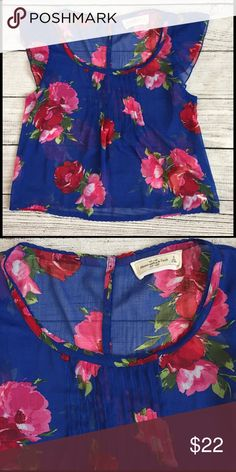 """Abercrombie & Fitch Feminine Floral Blouse Top S This top is absolutely adorable. ❤️ Done in a rich blue with shades of pink and red flowers. Buttons all the way down the back with tiny petite buttons. Has pin tucking on the front. Lightweight poly fabric. This is perfect for work, a romantic date night out, a bridal shower.......just perfect for the spring and summer. No rips or stains. Approximate measurements laying flat are… 18"""" chest and 19"""" long. Thanks for looking and have a great…"""