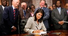 South Carolina Gov. Nikki Haley signs a bill into law as former South Carolina governors and officials look on Thursday, July 9, 2015, at the Statehouse in Columbia, S.C. The law enables the removal of the Confederate flag from the Statehouse grounds more than 50 years after the rebel banner was raised to protest the civil rights movement. (AP Photo/John Bazemore)