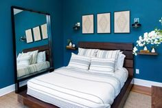 A low bed frame and oversized mirror both help to make the small bedroom feel bigger.