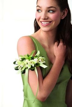 As sweetly feminine as she is.  Green cymbidium orchids and white spray roses are trimmed with mint green satin ribbon.