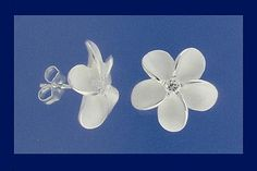 Sterling silver Hawaiian Plumeria (frangipani) stud earrings with a white frosted finish and an eye of sparkling clear cubic zirconia. Post back with spring butterfly clips.  Other matching items listed.   Measurements:Each flower 10mm diameter. Weight per pair, 1.45 grams.