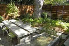 Contemporary Landscape Design with Wonderful Water Features : Fantastic Water Features For Modern Patio Design With Concrete Outdoor Dining Table And Armchairs With Green Cushions Perfected With Planting Beds And Green Trees Plus Wood Slat Fence