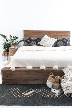 Dark sheets with a white comforter (and Pom poms?) and printed pillowcases