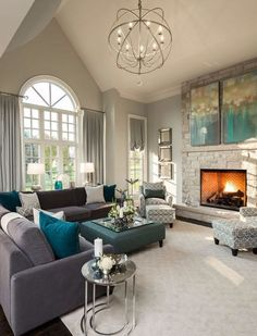 Living room decor - It's hard to say what came first; were the two paintings hung above the stonework fireplace inspired by the turquoise and charcoal gray of the furniture or was the furniture selected based on the paintings?