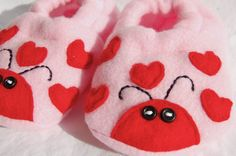 'Love Bug' booties are perfect for any Valentine's Baby! These baby booties are hand made to look perfect on any baby's foot! They are made with the softest polar fleece and embellished with cotton fabric and a fabric covered button. The button is sewn as well as glued to the flower to ensure safety. The elastic around the ankle is designed to gently stretch to fit a growing baby. They should fit babies approximately 0-9 months old, with a 4.5 inch sole.