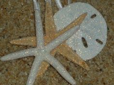 """Three beautiful ornaments to use all year long.     This set of ornaments contains:  1 White finger starfish about 3"""" wide  1 Natural starfish about 3"""" wide  1 Real sand dollar about 2"""" wide    All three are covered in a beautiful iridescence glitter. The glitter is very fine grit and looks amazing on them. They have been coated with a sealer, the glitter will NOT flake off. To top them off I used a white satin ribbon with a iridescence edge."""