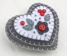 Handmade felt hanging heart with appliqued and embroidered flower and leaves in grey and white,with tiny red buttons for berries. 9cm x 8cm approx, with a cotton loop for hanging. A perfect gift or decoration . You can see more felt heart ornaments here;