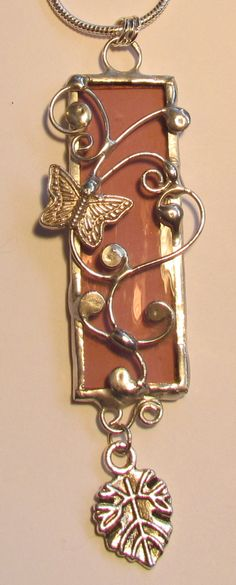 Stained glass pendant…silver soldered   glass with silver scroll accents.  Silver chain. $30