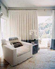 Living Room - A white slipcovered armchair beside white-and-blue curtains