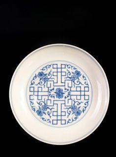 PLAT EN PORCELAINE BLEU BLANC CHINE, DYNASTIE QING, XIXEME SIECLE De forme circulaire, orné en son centre de pêches de longévité, de rinceaux feuillagés surmontés de motifs de ruyi, ornés de plusieurs registres de frises à motifs géométriques, sur la bordure et l'intérieur. Marque à six caractères de l'Empereur Yongzheng sous couverte à la base dans un double cercle. h 5 cm, d 21 cm