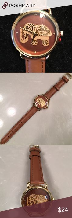"""Watch Brown with Gold Elephant in center Watch Elephant in the center looks gold on brown face.  Brown band adjustable.  Approximately 1 1/2"""" across the face of watch. Never been worn.  Stainless Steel Back. Has the red plastic at stem to save the battery. Geneva Accessories Watches"""