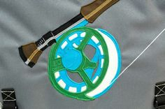 A closeup of the image on the fun waterproof flaptop bag with a fly reel graphic, done for Cheeky Fly Fishing.