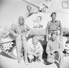 The crew of a Sherman tank pose beside their vehicle, decorated with a cartoon figure, during a break in fighting in the Western Desert, 29 October 1942. Note that three of the men are wearing American tank helmets, which were generally unpopular with British crews.
